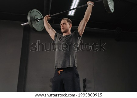 Strong man lifting barbell as a part of crossfit exercise routin Stock photo © Yatsenko