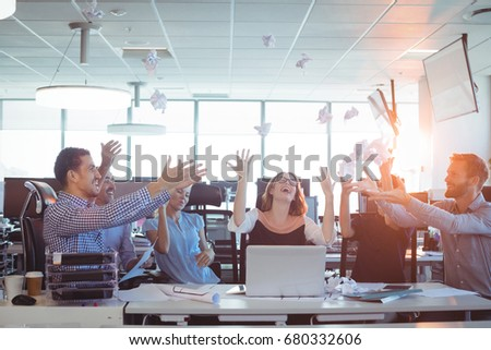 Cheerful business people tossing crumpled paper balls at desk in office Stock photo © wavebreak_media