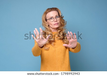 Confident woman keeping hands in stop gesture, trying to defend herself  Stock photo © ichiosea