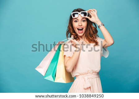 Shocked excited young woman posing isolated over blue background wall using mobile phone. Stock photo © deandrobot