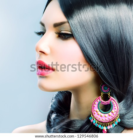 Portrait of beautiful brunette woman with big earring and shinny accessories. With hair around neck, Stock photo © studiolucky