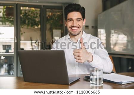 Happy portrait of businesslike man wearing white shirt sitting o Stock photo © deandrobot