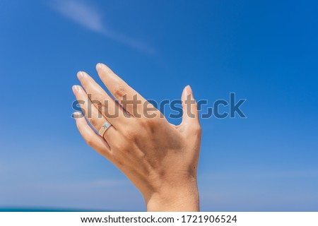 Stock photo: Female hand with a ring with a drawn plane holding a plane flying in the sky. Traveling on an airpla