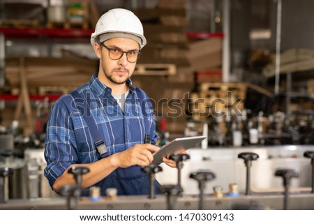 Young serious employee of industrial plant testing new technical equipment Stock photo © pressmaster