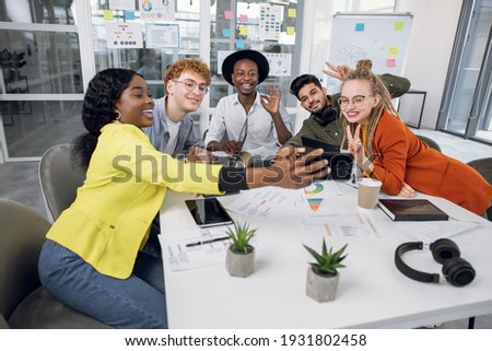 Front view of diverse good looking business colleagues discussing over digital tablet in modern offi Stock photo © wavebreak_media