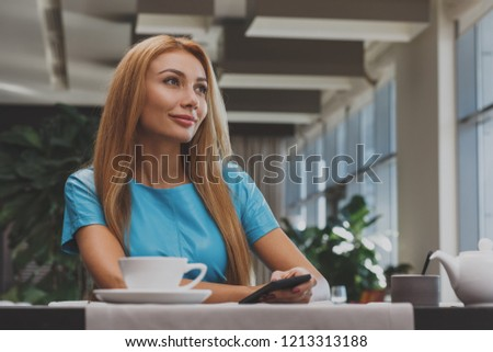 Gorgeous red-haired woman having her breakfast while sitting on her bed Stock photo © wavebreak_media