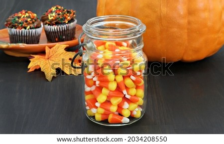 Candy corn in a rustic mason jar.  Pumpkin and cupcakes in the b Stock photo © rojoimages