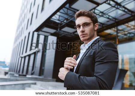 Business man in glasses standing sideways and looking at camera Stock photo © deandrobot