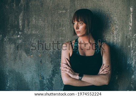 Portrait of a young serious sportswoman standing with arms folded Stock photo © deandrobot