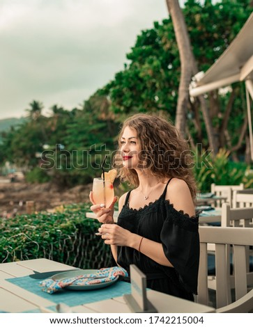 Portrait of beautiful woman with cocktail sitting on sun lounger Stock photo © wavebreak_media