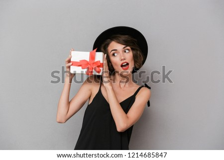 photo of surprised woman 20s wearing black dress and hat holding stock photo © deandrobot