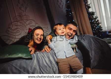 happy mother and son jumping on the bed against the backdrop of a large window overlooking the skysc stock photo © galitskaya