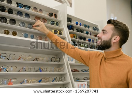 Happy young man taking pair of stylish eyeglasses from display of eyewear Stock photo © pressmaster