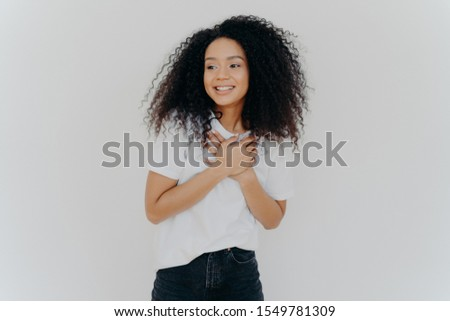 Photo of happy girl keeps both hands on chest, looks aside with pleasant smile, notices something aw Stock photo © vkstudio