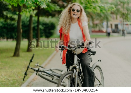 Pleasant looking young woman in sunglasses, rides sport bicycle, stops for break, enjoys beauty of n Stock photo © vkstudio
