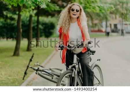 Agradável olhando mulher jovem óculos de sol esportes bicicleta Foto stock © vkstudio