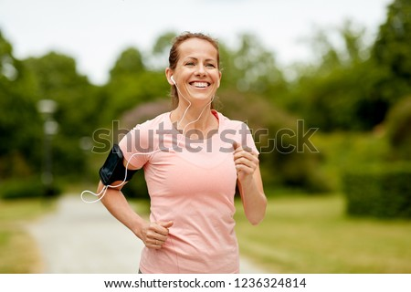 Happy summer running woman runner listening to music on phone sports armband with touchscreen and he Stock photo © Maridav