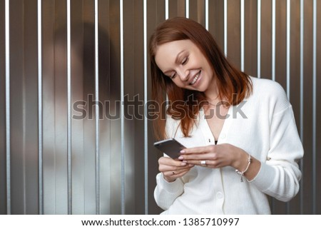 Positive successful European female economist makes money payment on website, poses with cell phone, Stock photo © vkstudio