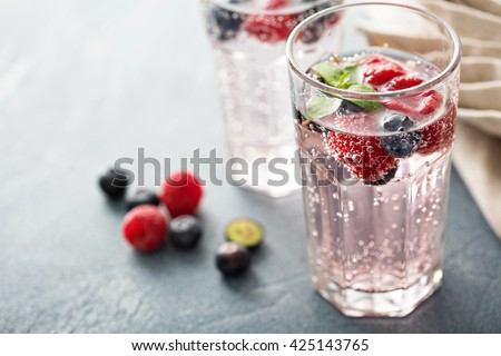 Glass of fresh sparkling water lemonade with mint and ice cubes on white background. Macro Stock photo © DenisMArt