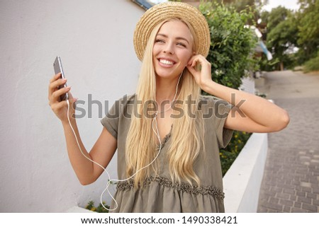 Photo of cheerful woman 20s wearing earphones smiling and holdin Stock photo © deandrobot