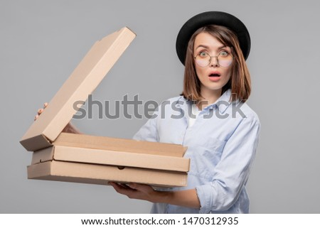 Astonished young woman in casualwear opening one of carton boxes Stock photo © pressmaster