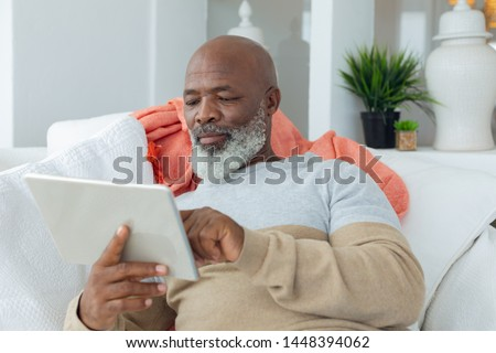 Front view of an active senior African American man using digital tablet while sitting on a wicker c Stock photo © wavebreak_media