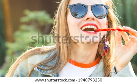 Image of cheerful blonde woman licking candy and smiling Stock photo © deandrobot