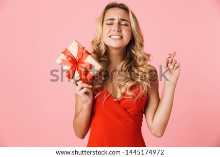 Portrait of blond woman 20s holding fingers crossed for pray or  Stock photo © deandrobot