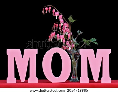 the word mom isolated on black with a vase of bleeding hearts stock photo © rojoimages