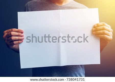 casual man holding blank a3 paper spread as copy space stock photo © stevanovicigor
