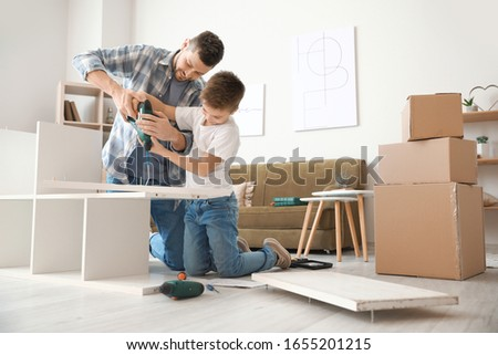 Father and son assembling furniture. Boy helping his dad at home. Happy Family concept Stock photo © galitskaya
