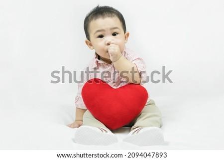 Stock photo: Baby boyin red shirt  sucking on his finger