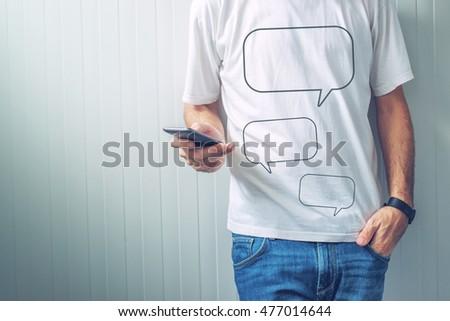 Guy with speech balloons printed on shirt using mobile phone Stock photo © stevanovicigor