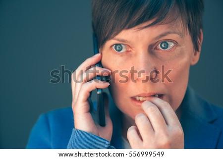 Nervous businesswoman bites fingernails during telephone convers Stock photo © stevanovicigor
