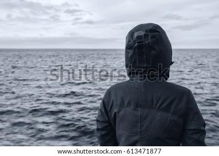 faceless hooded person looking at horizon over sea water stock photo © stevanovicigor