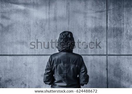 Unrecognizable hooded female person facing concrete wall as insu Stock photo © stevanovicigor