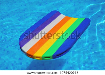 Rainbow pattern styrofoam swimming board floating in poolside wa Stock photo © stevanovicigor