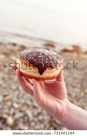 female hand holding chocolate donut at seaside beach stock photo © stevanovicigor
