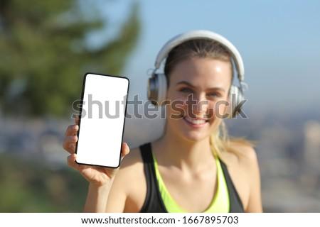 Stock photo: Female jogger listening music on mobile phone in front of graffi