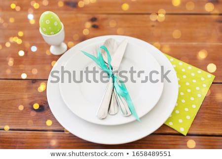 easter egg in cup holder, plates and cutlery Stock photo © dolgachov