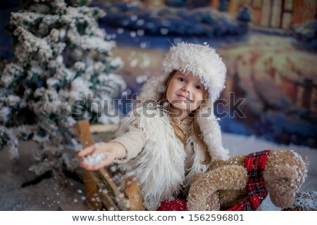A small child sits in a decorative wooden cart with hay, and holding in his hand a favorite toy stuf Stock photo © ElenaBatkova