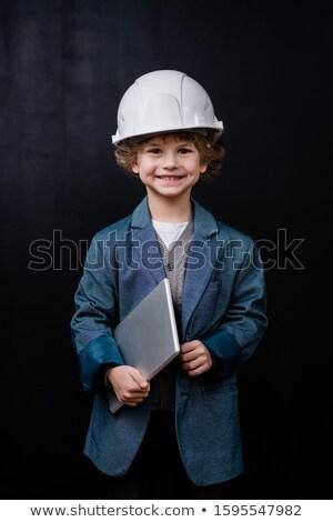 Cute smiling little boy in hardhat and formalwear holding folded laptop Stock photo © pressmaster