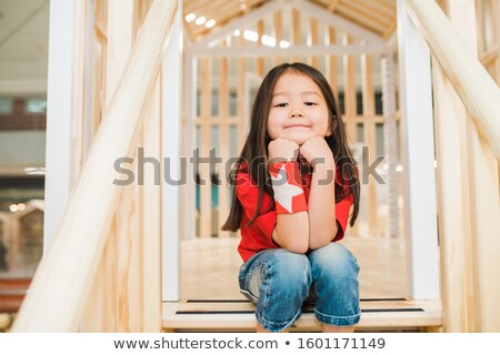 Restful little girl in blue jeans and red t-shirt sitting on wooden stairs Stock photo © pressmaster