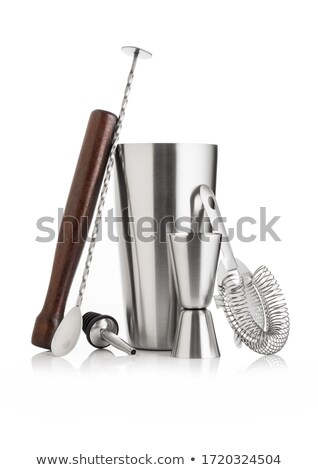 Cocktail set with black shaker and wooden muddler and measuring jigger with strainer on white. Stock photo © DenisMArt