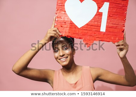Image of funny african american woman holding placard above her head Stock photo © deandrobot