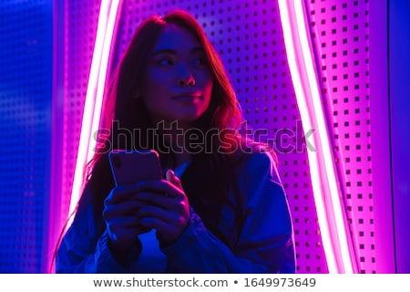 Woman posing over neon lights using mobile phone. Stock photo © deandrobot