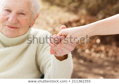 Senior woman's hand on a wheelchair Stock photo © Melpomene