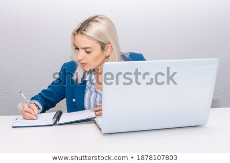 Blond woman writing in her agenda Stock photo © photography33