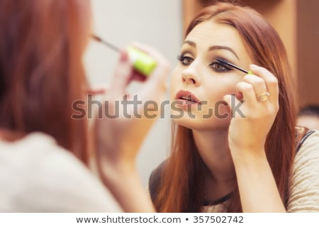 Woman applying make-up in mirror Stock photo © photography33