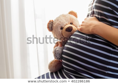 Stock photo: Pregnant woman holding teddy bear